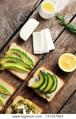 Avocado sandwiches with vegetables on dark wooden background