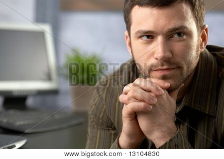 Determined office worker sitting at desk, thinking.