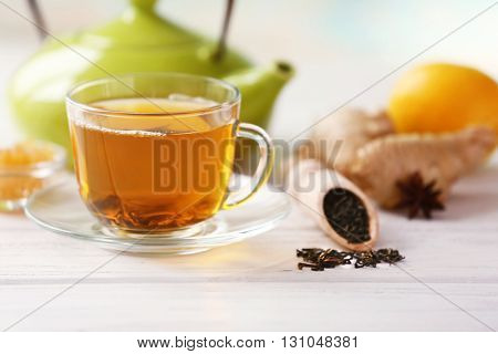 Glass cup of green tea with lemon and leaves on wooden table closeup