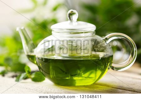 Teapot of green tea on wooden table