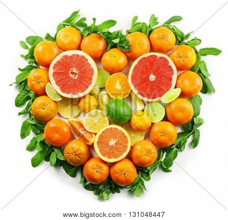Colorful orange tangerines positioned in a heart shape full of fruits with mint sprigs underneath it on a white background, top view