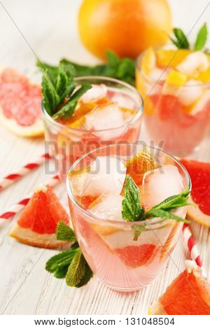Ripe grapefruits and fresh juice with mint, close up