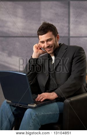 Mid-adult smiling office worker sitting in armchair using laptop computer.