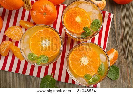 Delicious tangerine cocktails with sliced mandarins, ice and a mint, served  on a striped napkin, close up