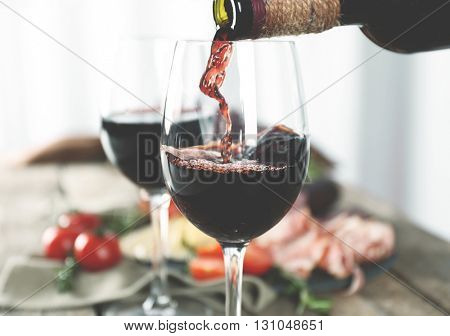 Pouring red wine into glass on wooden table closeup