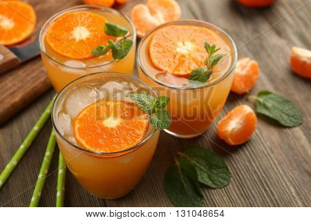 Delicious tangerine cocktails with sliced mandarins, ice, garnished with a mint, served on a wooden table, close up