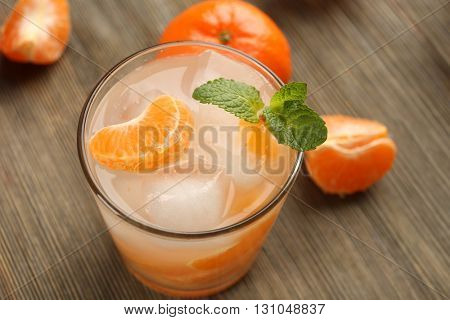 One fresh delicious tangerine cocktail with ice, mint and mandarins on the wooden table, close up