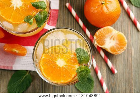 Tangerine cocktails with sliced mandarins, ice, mint with striped straws on a wooden table, top view