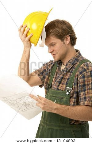 Young builder looking at floor plan, holding his hardhat. Isolated on white.