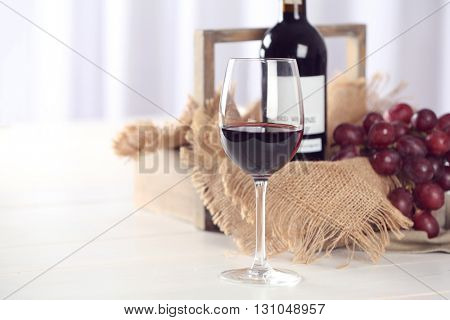 Glass and bottle of red wine with grape on blurred background