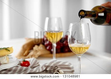 Pouring white wine into glass and food on table indoors