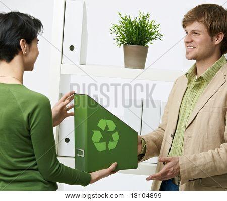 Happy office workers holding green folder with recycling symbol.