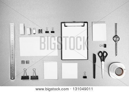 Office set with white sheets of paper, cup of coffee, watch and stationery on grey background