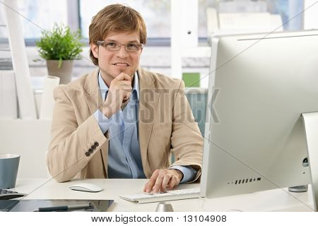 Young businessman sitting at office desk, looking at camera, thinking.