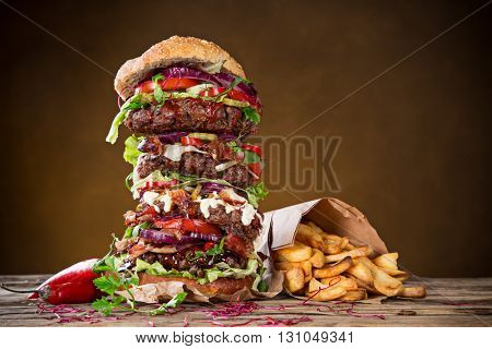 Close-up of home made tasty big burger on wooden table.