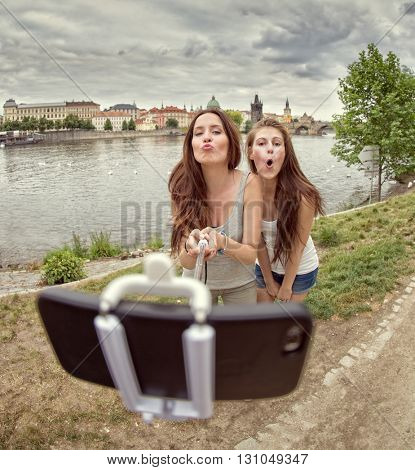 Friends making selfie. Two beautiful young women making selfie and grimacing