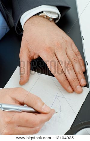 Hands of businessman drawing graph on paper napkin with pen.