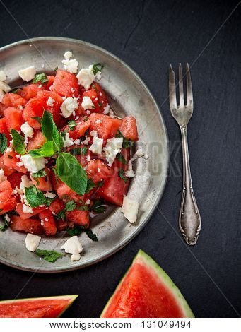 Fresh salad with water-melon, feta cheese, lime and mint. Close-up.