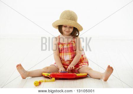 Kleines Mädchen sitzen auf Boden spielen mit Spielzeug Musikinstrument, Tagträumen over white Background.