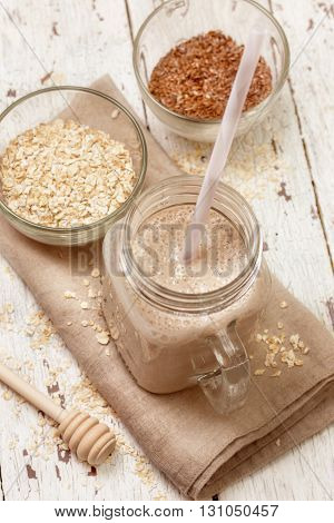 Smoothies with milk (soy almond coconut) oatmeal and flax seeds on a wooden background (top view)