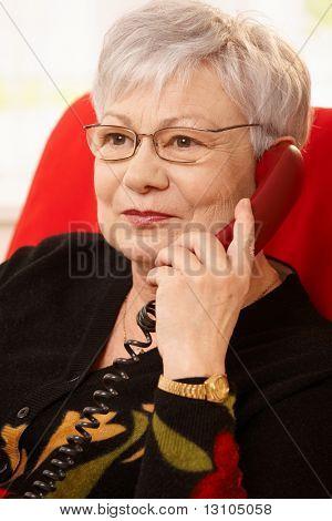 Closeup Retrato de mujer senior con teléfono en mano, con gafas, sonriendo.