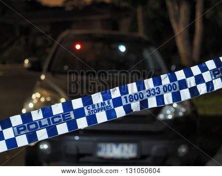 Melbourne, Australia -May 18, 2016: Blue and white Police tape cordoning off a car after dark like crime scene