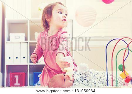 Happy Toddler Girl Feeding Her Baby Sister