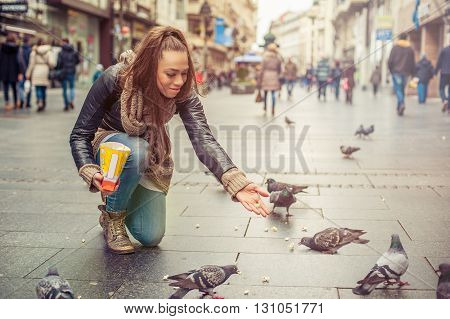 Young woman feeds pigeons on the street in the city
