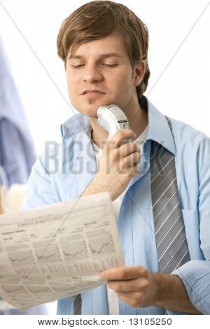 Young man shaving with electric razor, reading newspaper. Isolated on white