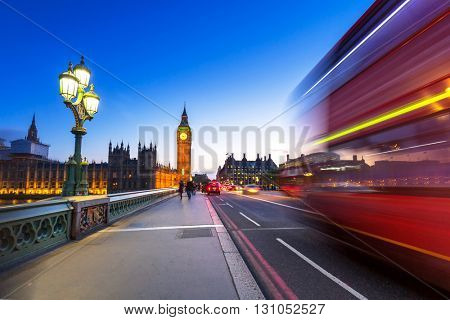 London scenery at Westminster bridge with Big Ben and blurred red bus, UK