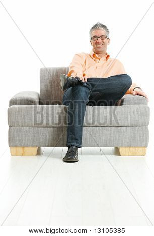 Happy man wearing jeans and orange shirt sitting on couch, talking on mobile phone. Isolated on white.