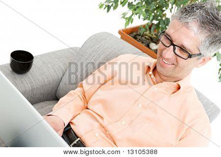 Happy man wearing orange shirt sitting on couch, browsing internet on laptop computer, smiling.