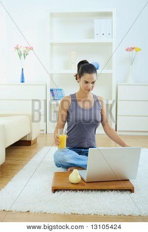 Lässig junge Frau mit Laptop-Computer, auf Fußboden im Wohnzimmer.