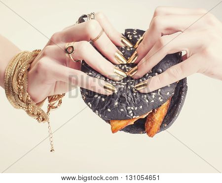 hands of rich woman with golden manicure and jewelry holding black hamburger close up, stylish summer concept