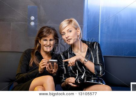 Young businesswomen sitting on couch at office lobby, using smart phone, smiling.
