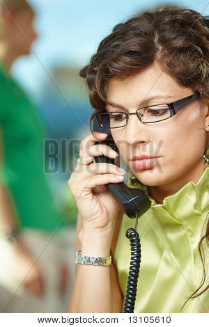 Young businesswoman sitting at desk in office, listening on landline phone.