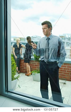 Business people talking on terrace outdoor of office building. Businessman in front using mobile phone. Through the window view.