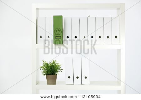 Imagem conceitual de pasta de conservação ambiental, verde com símbolo em uma prateleira o de completo de reciclagem
