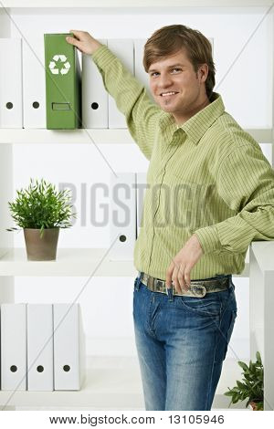 Young environmentalist man standing in office pulling out green folder,