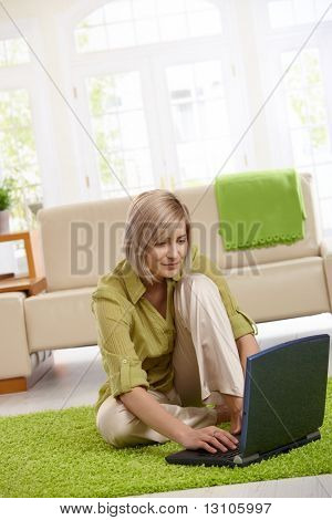 Smiling woman surfing the internet on laptop computer at home.