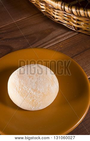 Traditional Japanese mochi on a brown saucer on a wooden table