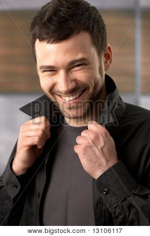 Trendy young man laughing at camera posing in stylish shirt.