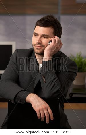 Portrait of young confident businessman listening to mobile phone call, smiling.