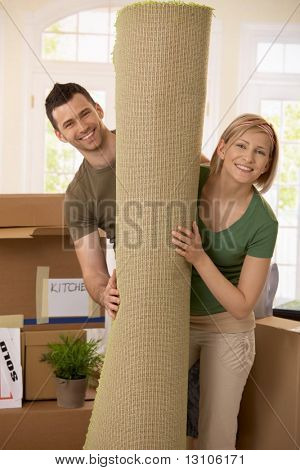 Portrait of smiling couple moving house, holding carpet rolled up, surrounded with boxes.