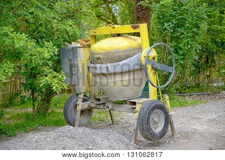 a yellow concrete mixer foliage in background