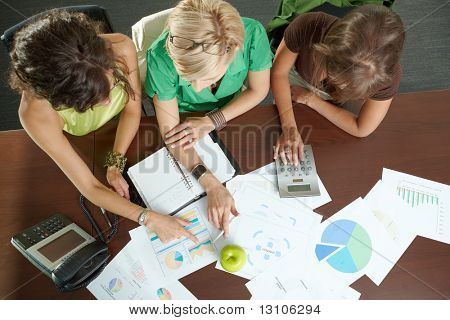 Young businesswomen sitting at table in meeting room, discussing finacial charts. Overhead shot.