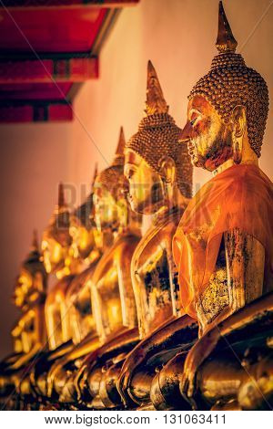 Travel Thailand Buddhism religion - vintage retro effect filtered hipster style image of row of sitting Buddha statues in Buddhist temple Wat Pho, Bangkok, Thailand
