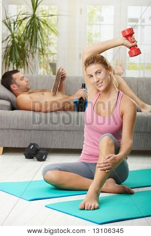 Young woman doing dumbbell exercise sitting on fittness mat at home, smiling. Man reading newspaper in background.