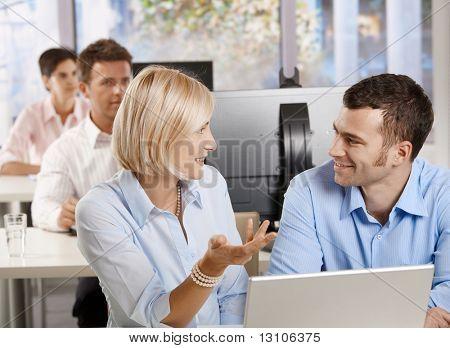 Junge Unternehmer sitzen am Schreibtisch mit Computer im Gespräch bei Business Seminar lächelnd.?