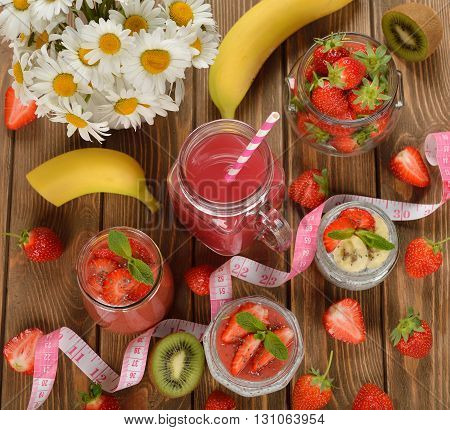 Diet desserts and drinks with chia seeds and strawberries on brown background
